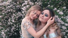 Twee zusters in de blauwe kleding van llight luxueuze wonderfull koesteren in de tuin dichtbij witte bloemen vrouwen van  stock footage