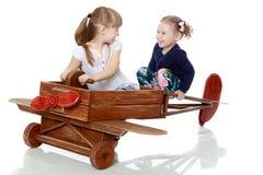 Twee zusters die in een houten vliegtuig spelen Royalty-vrije Stock Afbeeldingen