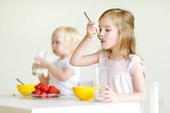 Twee zusters die graangewas met melk eten stock foto