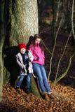 Twee zusters die in herfstbos stellen royalty-vrije stock afbeelding