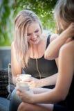 Twee zusters die koffie op een bank drinken Stock Foto
