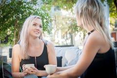 Twee zusters die koffie op een bank drinken Royalty-vrije Stock Afbeeldingen