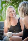 Twee zusters die koffie op een bank drinken Royalty-vrije Stock Foto's