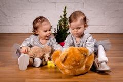 Twee zusters die met teddybeer naast de Kerstboom spelen Royalty-vrije Stock Afbeeldingen