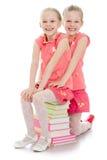 Twee zusters die op de boeken zitten royalty-vrije stock afbeelding