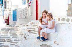 Twee zusters die op de treden op de Griekse straat zitten royalty-vrije stock foto