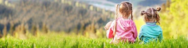 Twee zusters die op het gras zitten en bekijken de bergen bann stock foto's