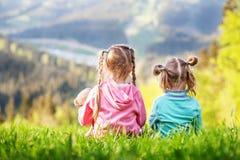 Twee zusters die op het gras zitten en bekijken de bergen E royalty-vrije stock afbeelding