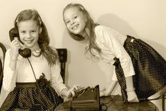 Twee zusters die op oude telefoon spreken Stock Afbeeldingen