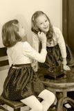Twee zusters die op oude telefoon spreken Stock Foto's