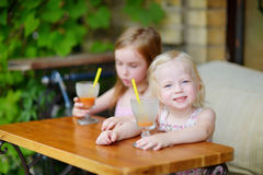 Twee zusters die sap in openluchtkoffie drinken Royalty-vrije Stock Foto