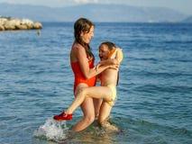 Twee zusters die spelen spelen en in het overzees zwemmen royalty-vrije stock foto
