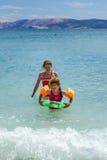 Twee zusters die spelen spelen en in het overzees zwemmen stock afbeeldingen