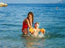 Twee zusters die spelen spelen en in het overzees zwemmen stock fotografie