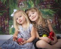 Twee Zusters die voor Kerstmisbeelden stellen Stock Foto's