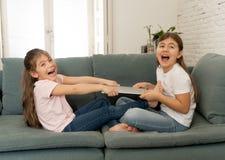 Twee zusters die voor laptop computer vechten Kinderen en technologieverslaving royalty-vrije stock foto