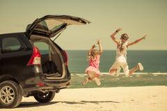 Twee zusters die zich dichtbij een auto op het strand bevinden Royalty-vrije Stock Foto's