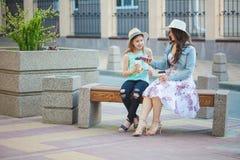 Twee zusters, een mooi donkerbruin in de stad lopen, op een bank zitten en meisje en een jong meisje die, het lachen spreken Royalty-vrije Stock Foto's