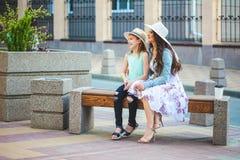 Twee zusters, een mooi donkerbruin in de stad lopen, op een bank zitten en meisje en een jong meisje die, het lachen spreken Royalty-vrije Stock Fotografie