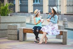 Twee zusters, een mooi donkerbruin meisje en een jong meisje die in de stad lopen, die op een bank met koffie in handen zitten en Stock Afbeeldingen