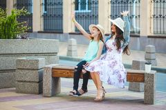 Twee zusters, een mooi donkerbruin meisje en een jonge meisjesgang in de stad, zitten op een bank en spreken, lach en golven hun Royalty-vrije Stock Foto