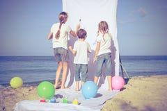 Twee zusters en broer het spelen op het strand in de dagtijd Royalty-vrije Stock Fotografie