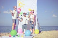 Twee zusters en broer het spelen op het strand in de dagtijd Stock Afbeeldingen