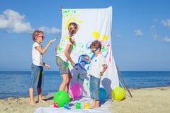 Twee zusters en broer het spelen op het strand in de dagtijd Royalty-vrije Stock Afbeelding