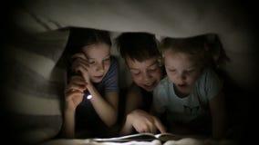 Twee zusters en een broer lezen een boek onder een deken met een flitslicht in een donkere ruimte bij nacht De jonge geitjes spel stock footage