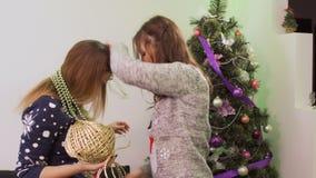 Twee zusters hebben pret tijdens het verfraaien van Kerstboom stock video