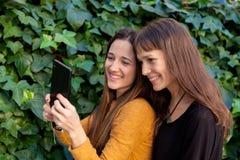 Twee zusters het genieten van van een dag met mobiel Stock Afbeelding