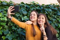 Twee zusters het genieten van van een dag met mobiel Royalty-vrije Stock Afbeelding