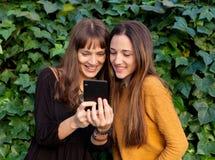 Twee zusters het genieten van van een dag met mobiel Royalty-vrije Stock Foto's