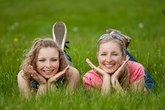 Twee zusters leggen op het gras Stock Afbeeldingen