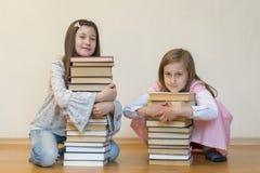 Twee zusters met een stapel van boeken op de vloer in de ruimte Het concept onderwijs en ontwikkeling van kinderen Liefde van royalty-vrije stock foto