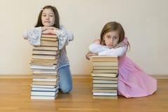 Twee zusters met een stapel van boeken op de vloer in de ruimte Het concept onderwijs en ontwikkeling van kinderen Liefde van stock afbeelding