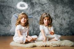 Twee zusters met engelenvleugels stock afbeeldingen