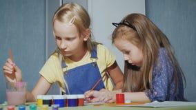 Twee zusters met enthousiasme schilderen de kleuring van waterverf stock video