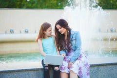 Twee zusters, mooi donkerbruin meisje en jong meisje in de stad, het zitten door de fontein lopen en het spreken die, die bekijke stock foto