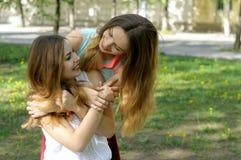 Twee zusters omhelzen het genieten van van vergadering Stock Afbeelding