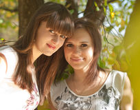 Twee zusters onder gele bladeren Stock Foto's