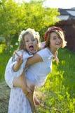 Twee zusters stoeien op het gazon in de zomer Stock Afbeeldingen