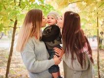 Twee zusters van de tweelingen, tribune in een de herfstpark, kus op beide wangen van een kleine jongen, die één van hen houdt stock fotografie