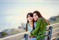Twee zusters, vrienden die door meer samen zitten Royalty-vrije Stock Foto