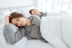 Twee zusterstweelingen die en in bed samen liggen slapen Royalty-vrije Stock Afbeeldingen