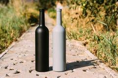 Twee zwarte en grijze flessen op de weg van de tegels, het dorp, landelijk alcoholisme, dronkenschap alcoholische ziekte natuurli royalty-vrije stock afbeeldingen