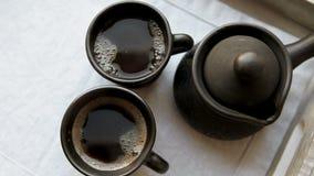 Twee zwarte koffiekoppen en klei ibrik op het houten presenteerblad stock videobeelden