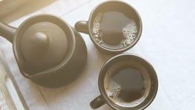 Twee zwarte koffiekoppen en klei ibrik op het houten presenteerblad stock video