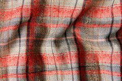 Tweed fabric in a red-gray cell crumpled stock photography
