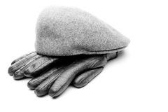 Mens accessories studio quality white background. Tweed grey cap black leather gloves white background Royalty Free Stock Images